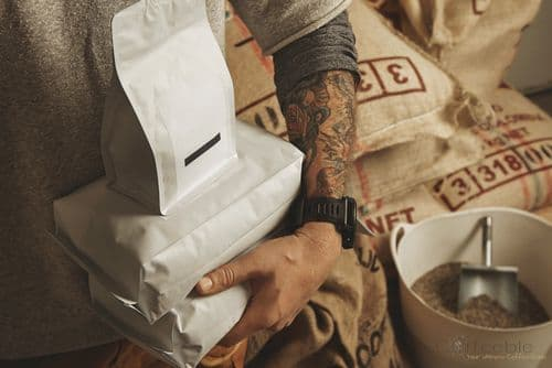 Tattooed barista holds coffee packages for shipping