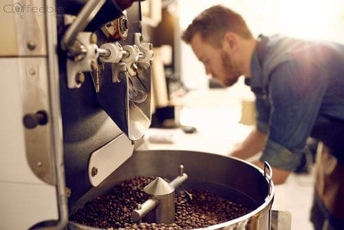 coffee beans in roasting machine and roaster in background