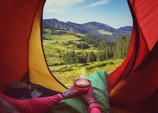 woman lying in tent with cup of instant coffee