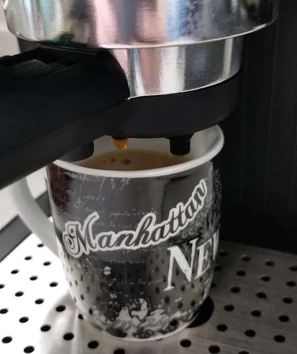 An image of espresso brewing into a cup through a portafilter