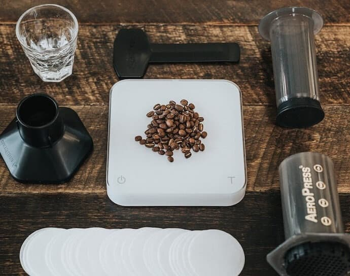 a disassembled aeropress, some filters, and a mound of coffee beans on a scale