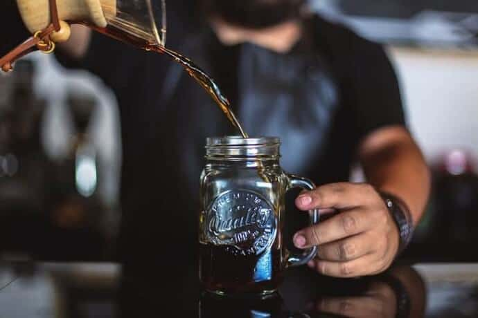 a guy showing how to make cold brew coffee at home using a mason jar