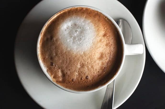 a cup of cappuccino on white saucer