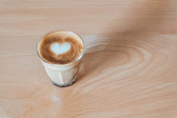 a latte drink with a heart-shaped art