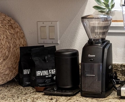 some bags of coffee beans and the baratza encore, which is one of the best burr coffee grinders in out list.
