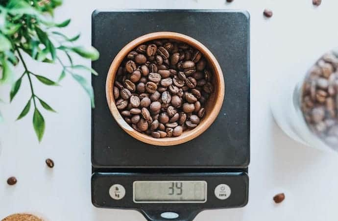 a container with coffee beans on one of our favorite coffee scales for brewing coffee