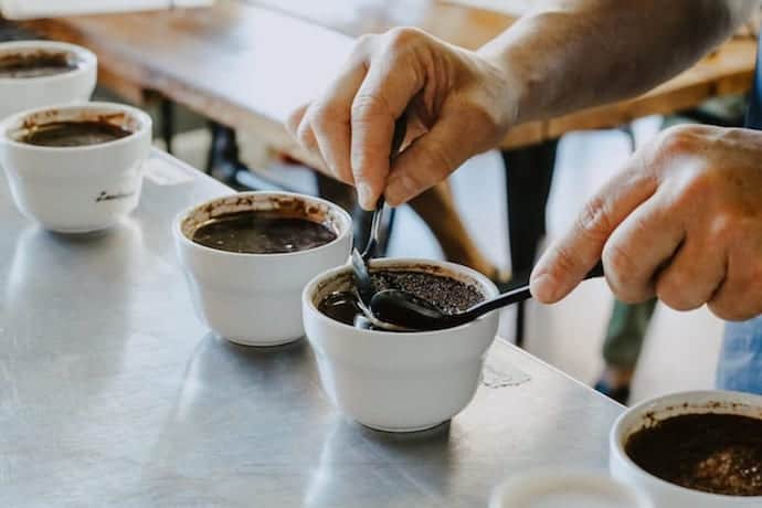 a pair of hands and the best coffee beans used for cupping