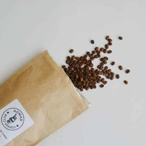 Coffee beans spilling from  the Nomad Coffee Subscription bag